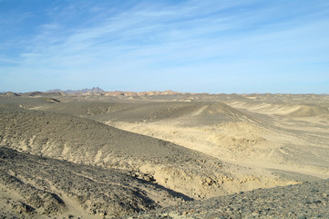 Egyptian desert covered by black stones and blue sky.