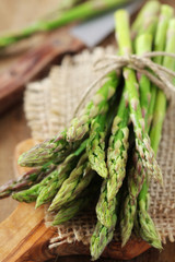 Bundle of fresh green asparagus on a wooden cutting board