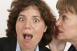 two women whisper a secret in close up