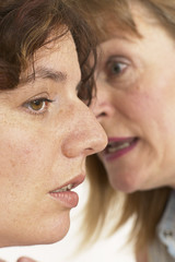 two women whisper a secret in close