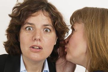 two women whisper a secret