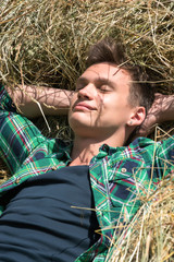 Young man relaxing in haystacks