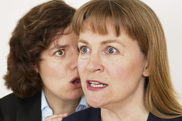two women whisper a secret in close up
