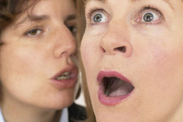 two women whisper a secret
