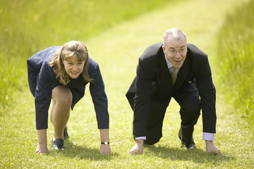 Business man and woman line up to compete in race on grass track