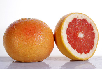 Grapefruit with half on white background
