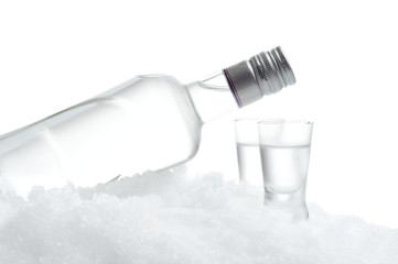 Bottle and glasses of vodka lying on ice on white background