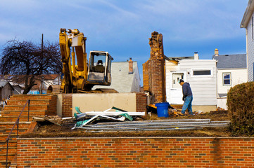 A large backhoe demolishes an old building