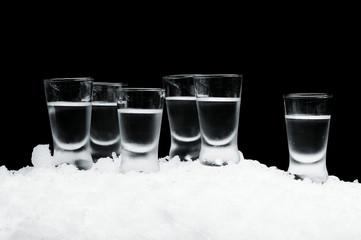 Many glasses of vodka standing on ice on black background