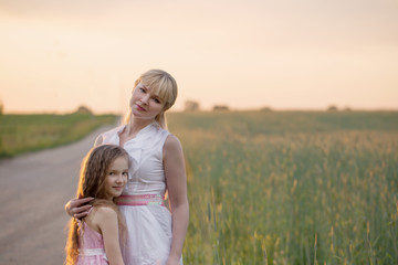 mother and daughter walking by the road in the wheat field on su