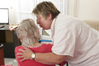 Cheerful care giver helping elderly woman at home, embracing her
