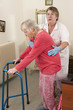 Care giver helping elderly woman to walk with a walker