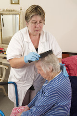 Friendly nurse cares for an elderly woman combing her hair