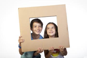 Niños usando cartón como marco