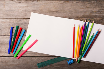 paper and colorful pencils on the wooden table