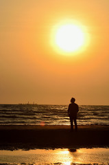 Silhouette man on beach with sunset sky background