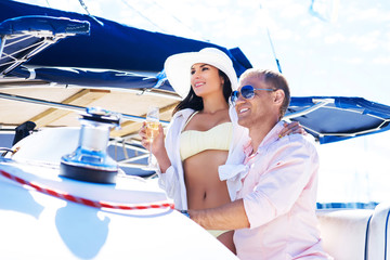 Young, attractive and rich couple have a party on a boat