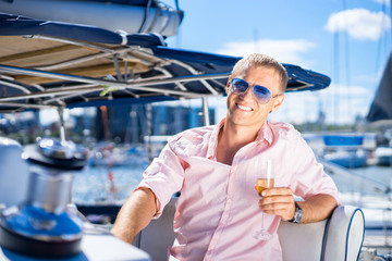 Handsome man in sunglasses relaxing on a boat