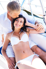 Rich man and a beautiful and sexy woman on a sailing boat