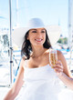 A young woman in a hat holding champagne on a boat