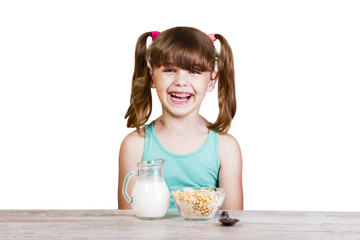 5-6 years old girl has breakfast corn flakes and milk