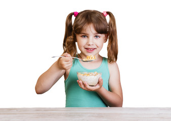 5-6 years girl eating breakfast cereal with milk  cornflakes