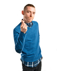 Young man doing a money gesture over white background