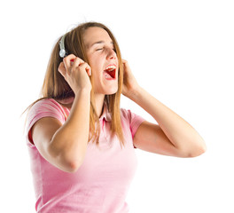 Young blonde girl listening music over white background