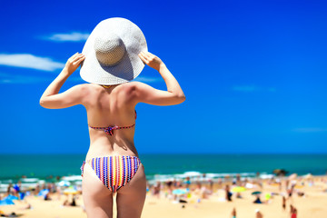 Woman in big sunhat on a beach