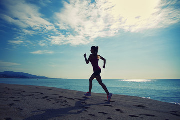 Silhouette of beautiful female jogger runs along the sea