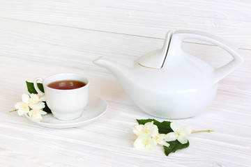 Cup with jasmine tea on a light wooden background