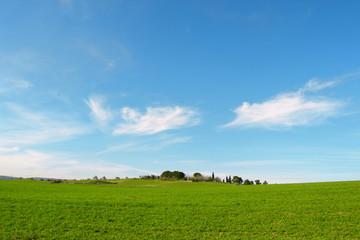 Collina con prato verde e cielo azzurro con nuvole
