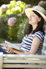 Woman relaxing with book in garden