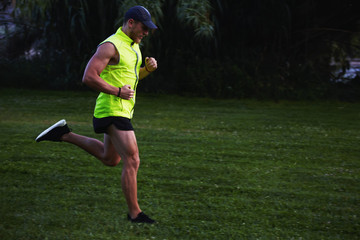 male runner jogging outdoors with tree's and grass on background