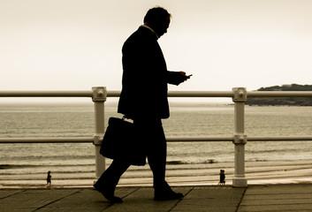 Ejecutivo con maletín caminando por la ciudad