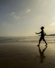 Anciana paseando por la playa
