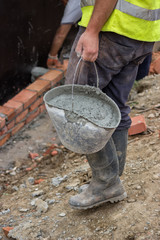 Worker bringing a bucket of mortar