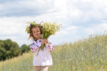 Beautiful smiling girl with bunch of wild flowers