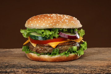 Tasty hamburger on wood background. Lots of ingredients