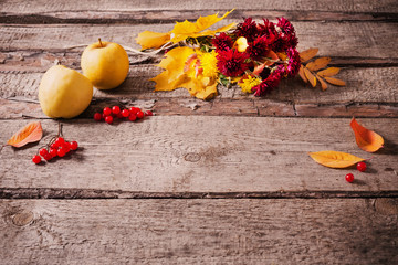 autumn flowers and leaves on wooden background