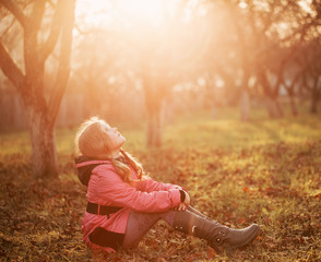 girl on grass in autumn garden
