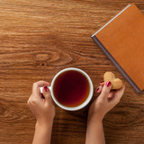 woman holding hot cup of tea with cookies