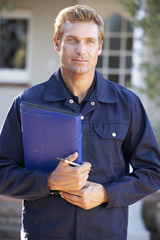 Man in overalls holding folder