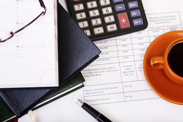 Calculator,pen, notebook and business reports. Coffee Break