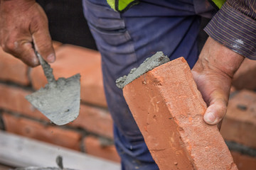 Builder worker with trowel building clay brick wall