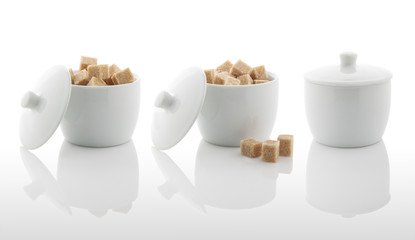 White sugar bowl and brown sugar cubes