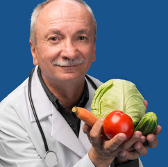 Senior male doctor holding vegetables