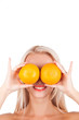 blond girl holds two oranges in front of eyes