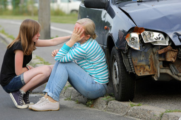 Woman sitting near the car after accident with her daughter