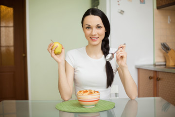 brunette girl having breakfast with muesli and apple at home in